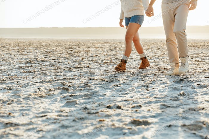 Couple outdoors at beach walking.