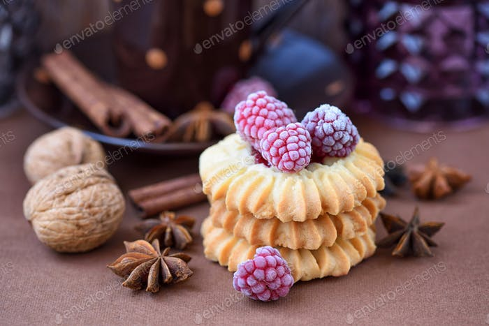 Shortbread cookies with frozen raspberries on brown background