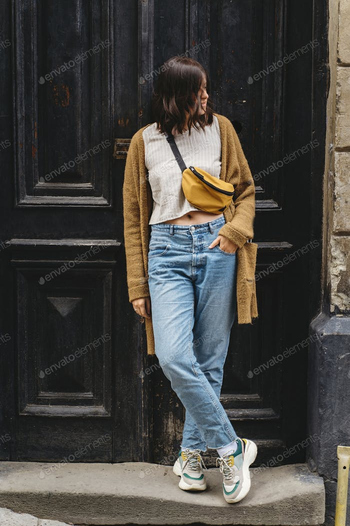 Stylish hipster girl standing at building in european city street