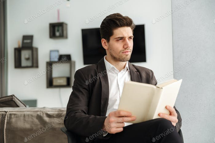 Serious young businessman sitting in home