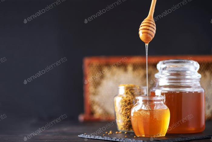 Bee pollen granules, honey jar with wooden dropper, honeycomb