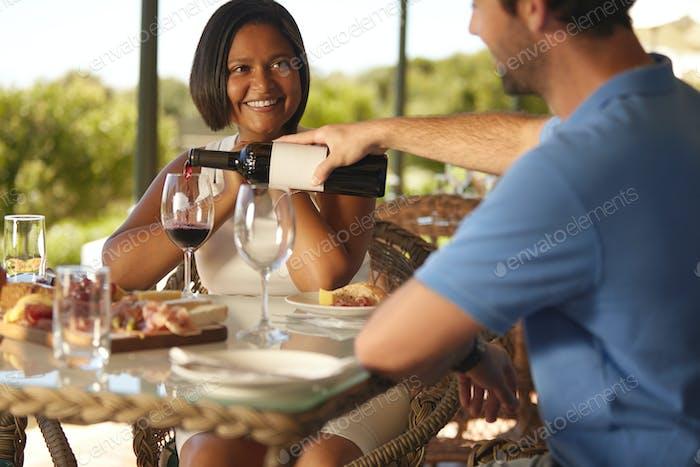 Couple enjoying red wine at winery restaurant