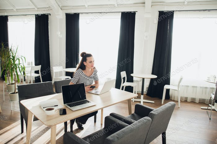 Young attractive woman is sitting at the table in a cafe with her laptop and working while looking