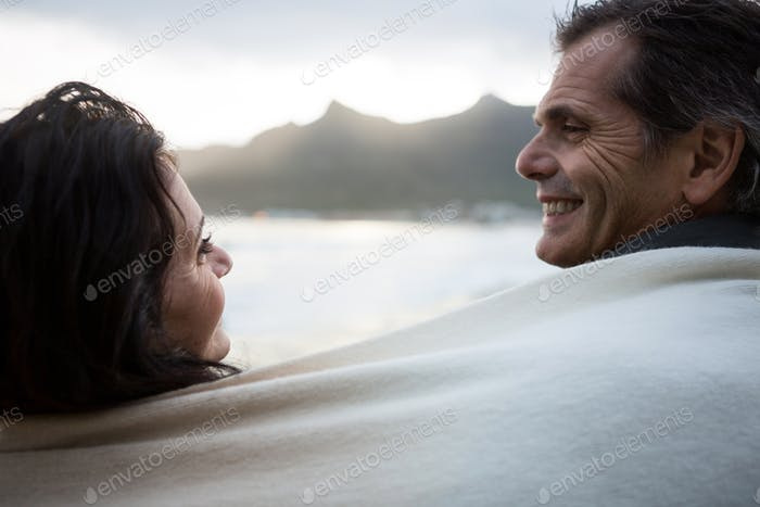 Couple wrapped in shawl looking at each other on beach