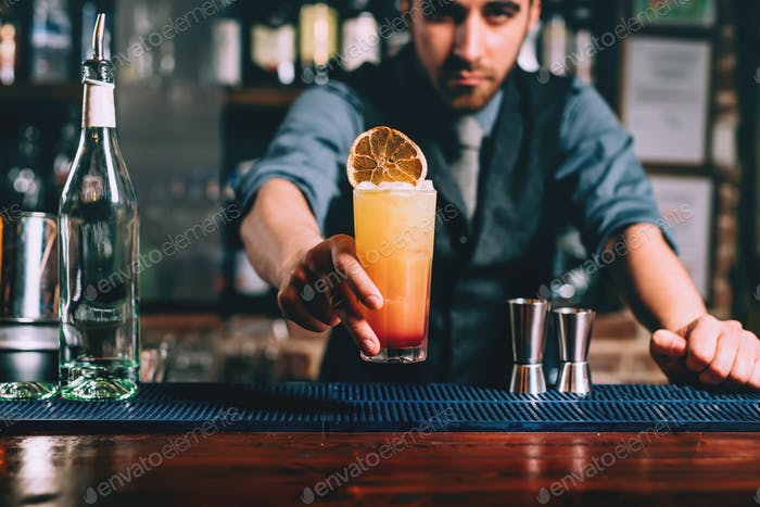 Portrait of handsome bartender serving perfect summer drink