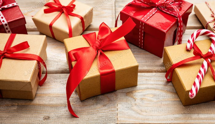 Gift boxes with red ribbons on wooden background