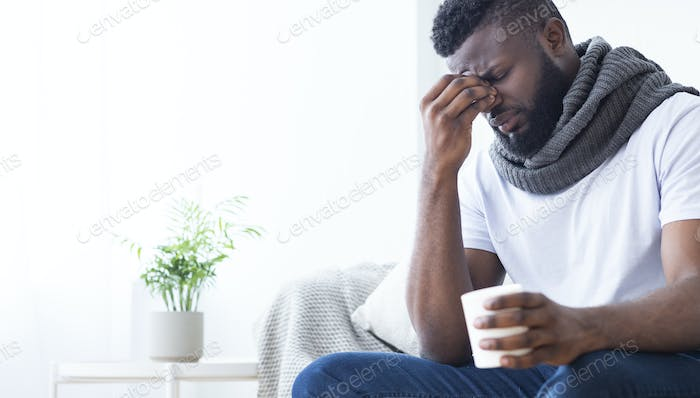 Black man with flu warming with cup with hot tea at home