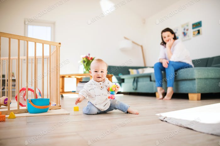 A baby boy playing on the floor at home, mother in the background.