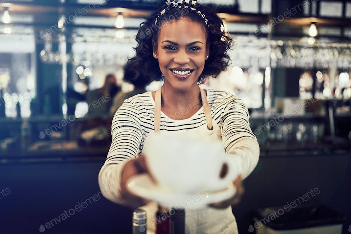 Young barista smiling and holding a fresh cup of coffee