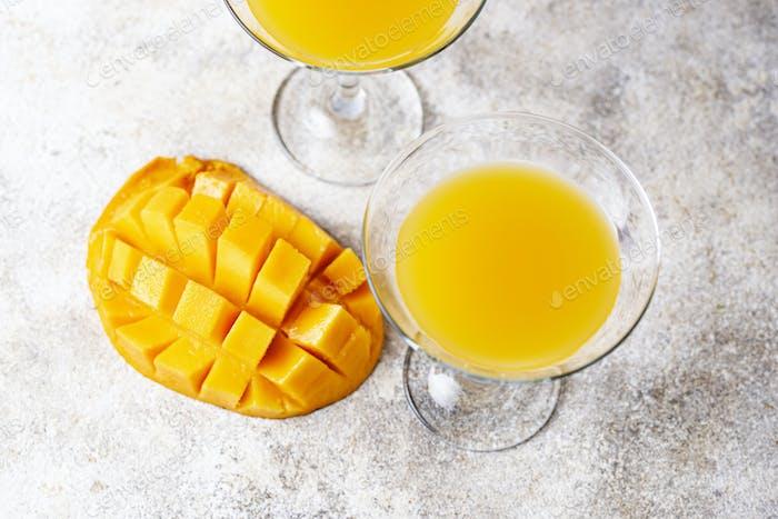 Tropischer Cocktail mit Mango auf hellem Hintergrund