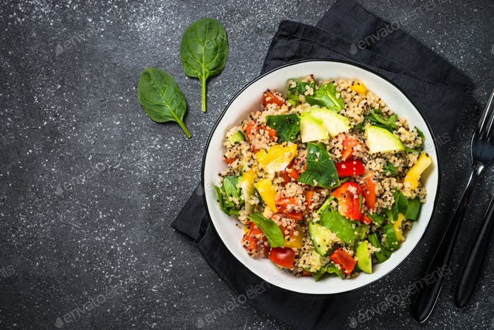 Quinoa salad with fresh vegetables on black