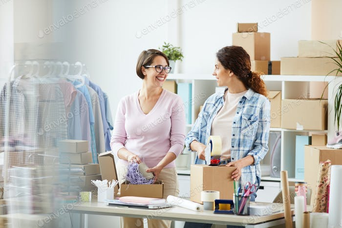 Happy young office managers preparing and packing orders of online clients