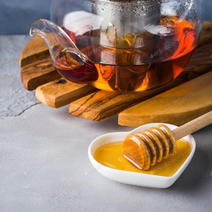 Teekanne aus rotem Tee und Honig