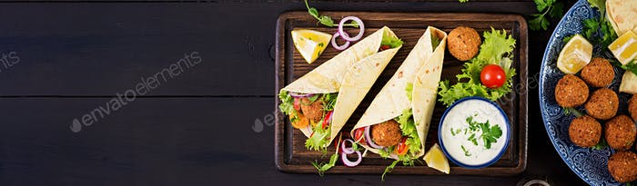 Tortilla wrap with falafel and fresh salad. Vegan tacos. Vegetarian healthy food. Banner. Top view