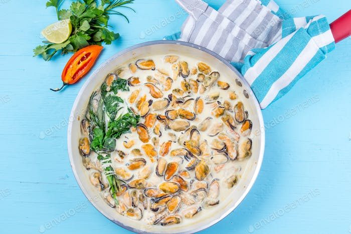 Mussels in milk cream y sauce with aromatic herbs and lemon in red cooking pan. Blue background.