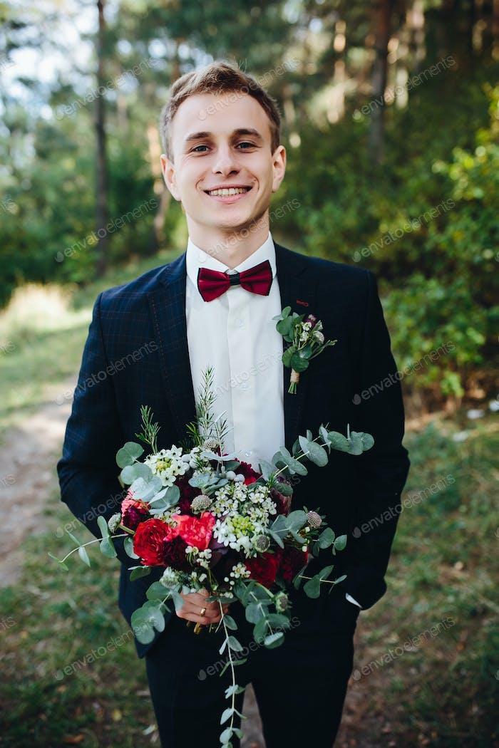 Bräutigam hält Blumenstrauß