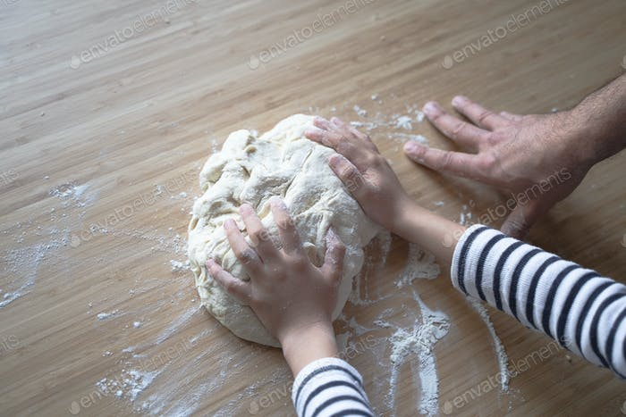 little Caucasian girl working the dough with her father on a wood cutting board
