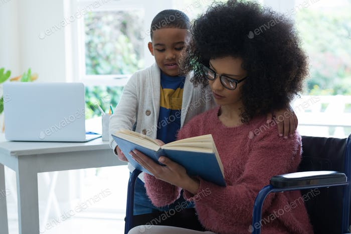 Son and his disabled mother reading a book