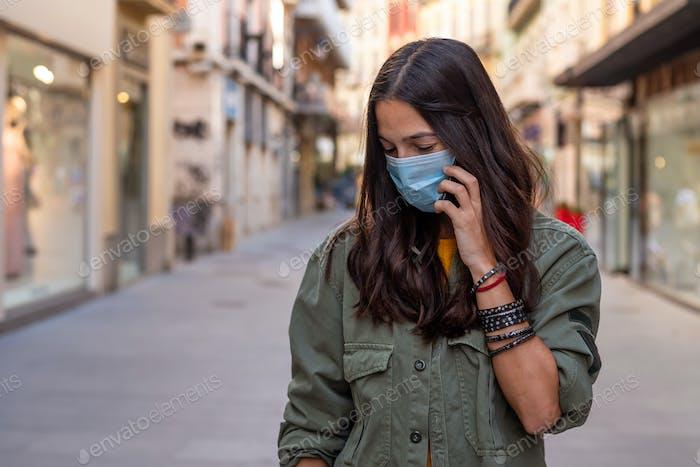Frau auf der Straße mit Maske und Telefon