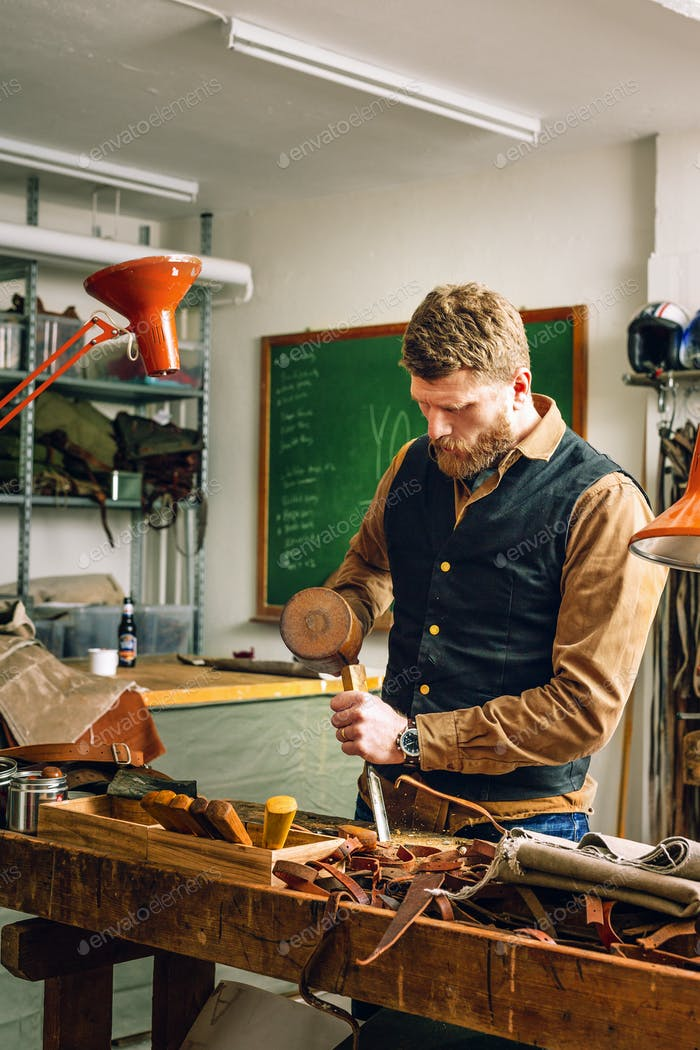 Man using mallet and chisel to cut belt in workshop
