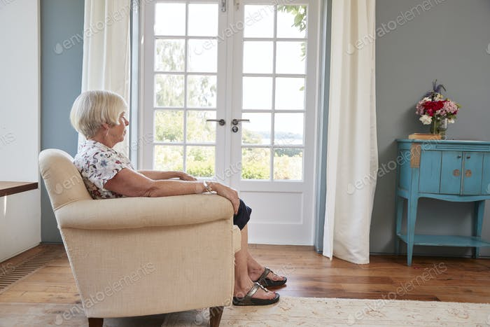 Senior woman sitting alone in an armchair at home