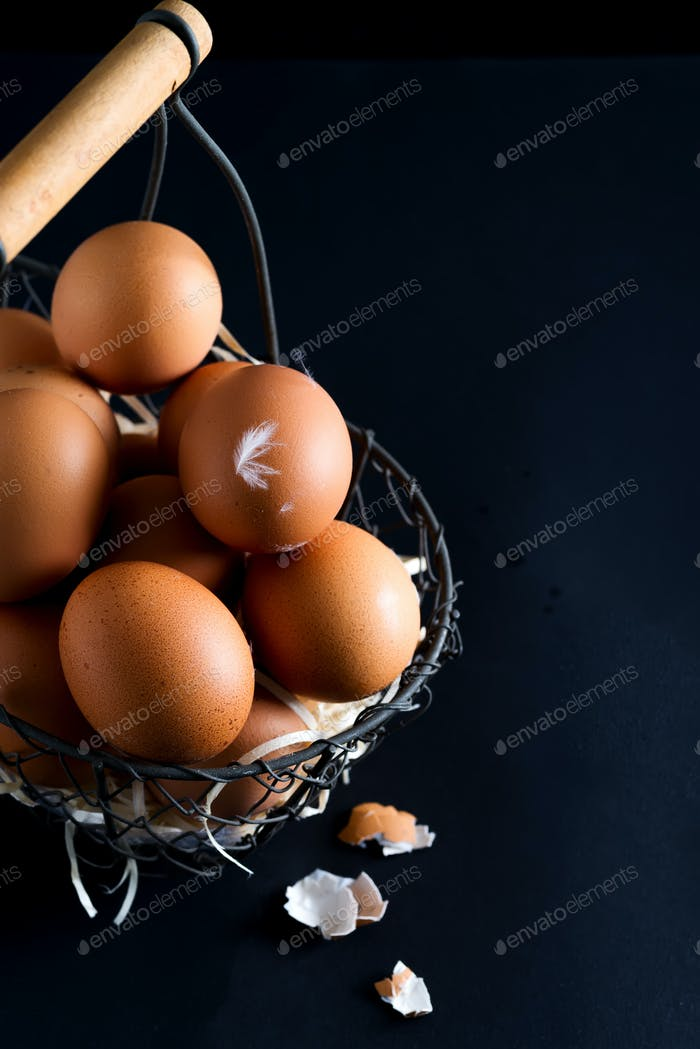 Basket with close up fresh farm natural chicken eggs on a black background. Easter congratulation