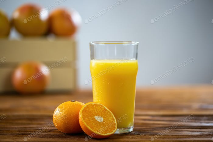 Glass of fresh orange juice on wooden table with grapefruits in background
