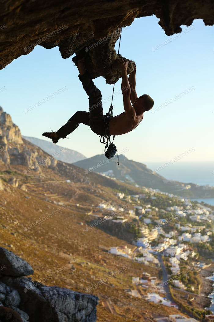 Young man climbing on roof of cave