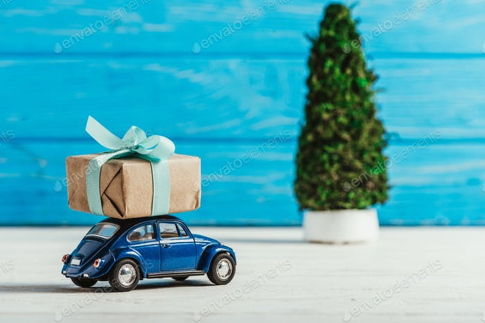 close-up shot of toy car with gift box and miniature christmas tree on blue wooden background