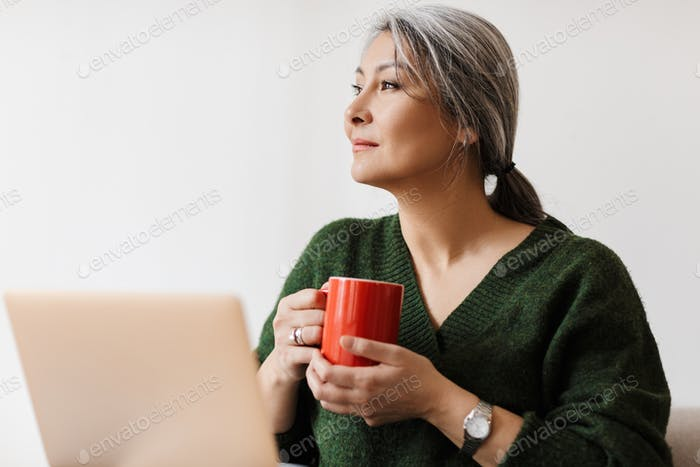 Image of beautiful adult asian woman using laptop computer at home