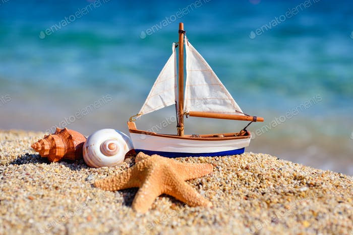 Toy ship and seashells on sand near sea. Summer vacation concept