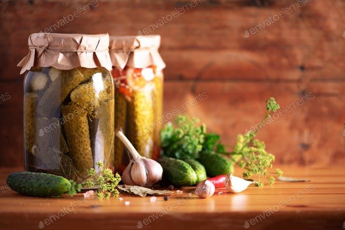 Pickled cucumbers in cans over wooden background. Copy space. Canned or fermented food. Harvest