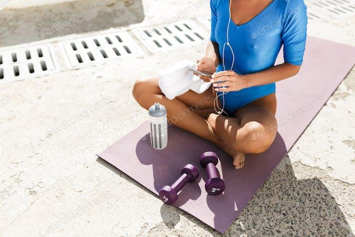 Frau Körper in blau Badeanzug sitzt auf Yoga-Matte in Lotus Pose mit Handy in den Händen