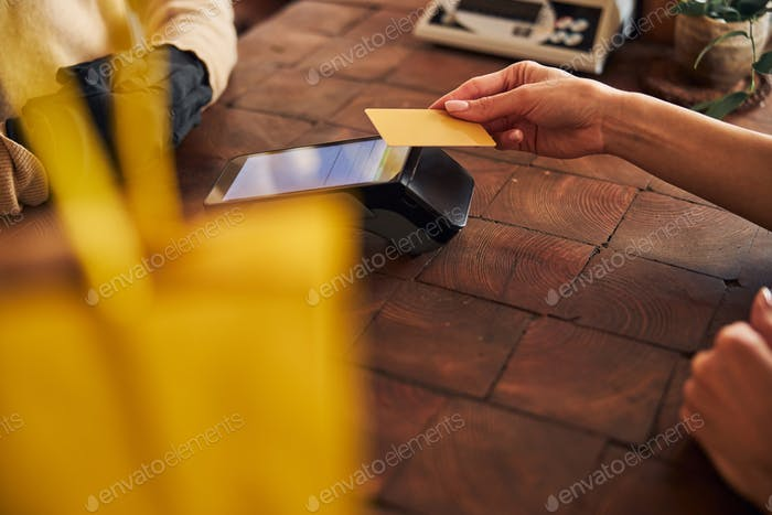 Young woman paying for purchases with credit card