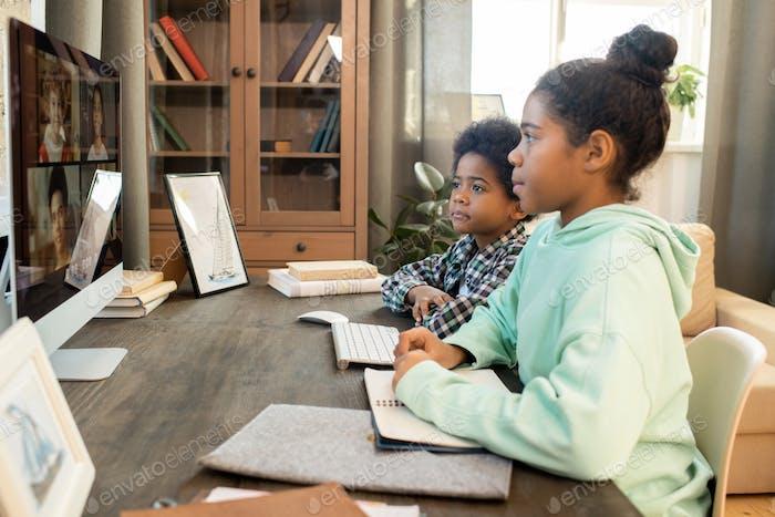 Escolares diligentes sentados frente al monitor de la computadora durante la lección en línea