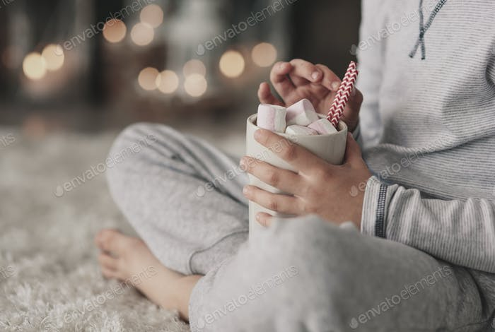 Boy in pajamas drinking hot chocolate