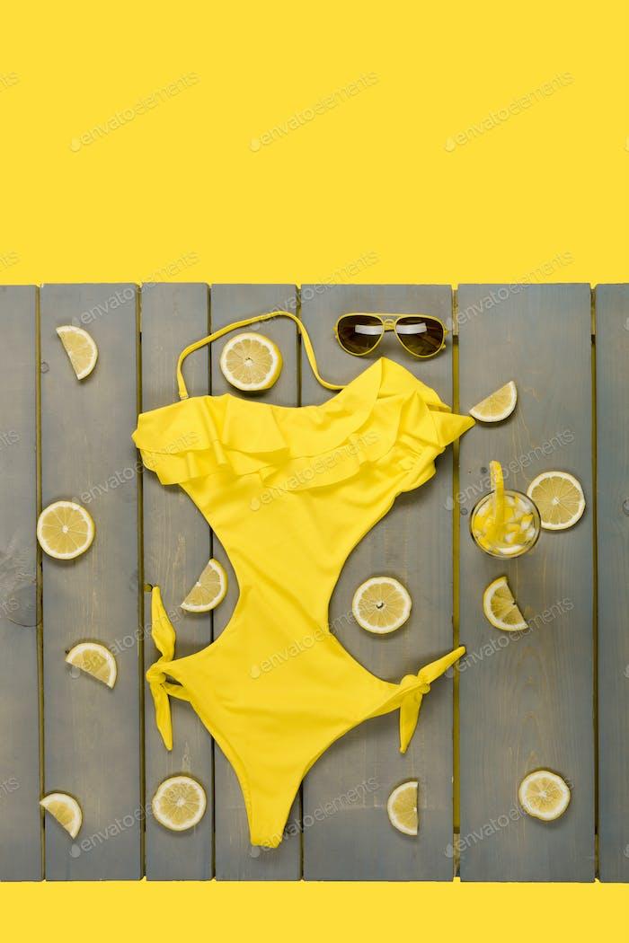 Bañador amarillo de una sola pieza, gafas de sol aviador entre partes de limones sobre Panel de De madera gris.