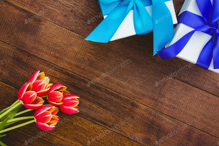 Close up view of red flowers and blue gifts