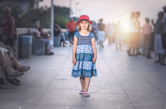 Little girl walking on a seaside promenade