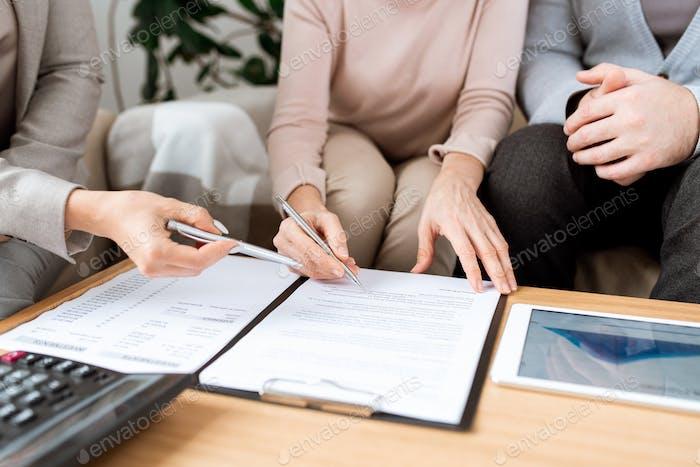 Junger Agent erklärt reifen Kunden, wo man Vertrag nach Verhandlungen unterzeichnen