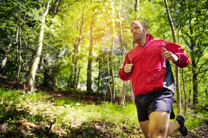 Fit young man cross country running along a forest trail