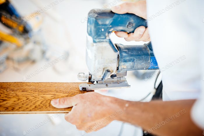 male industrial worker builder working with electric jigsaw and wood