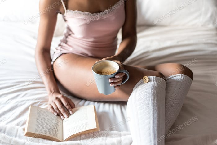 woman reading a book and drinking coffee on bed with socks