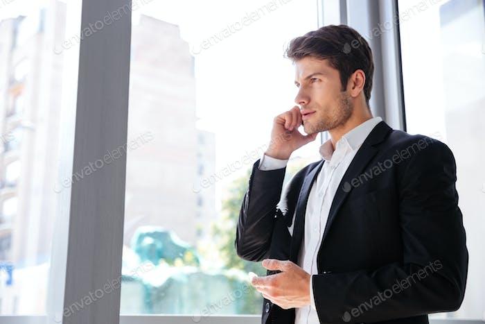 Businessman talking on mobile phone near the window in office