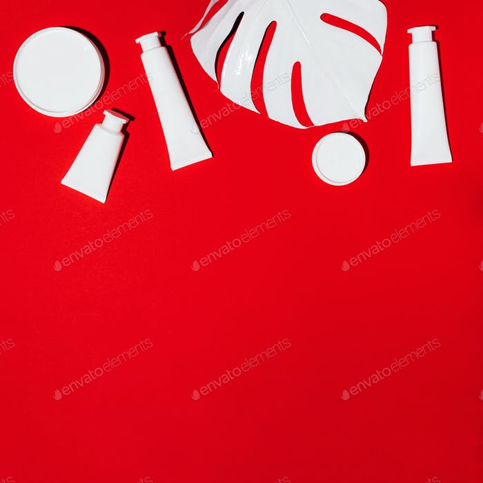 White bottles of skin care creams, monstera leaf over red background with copy space. Top view. Flat