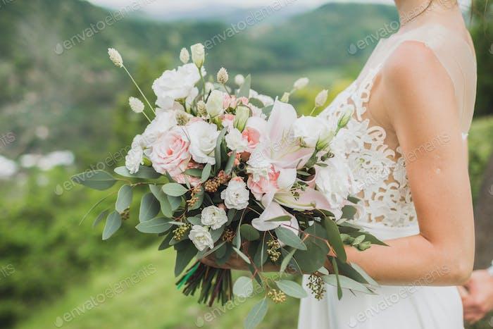 Braut hält sanften Hochzeitsstrauß mit Lilie, rosa Rosen und Grüns in den Händen