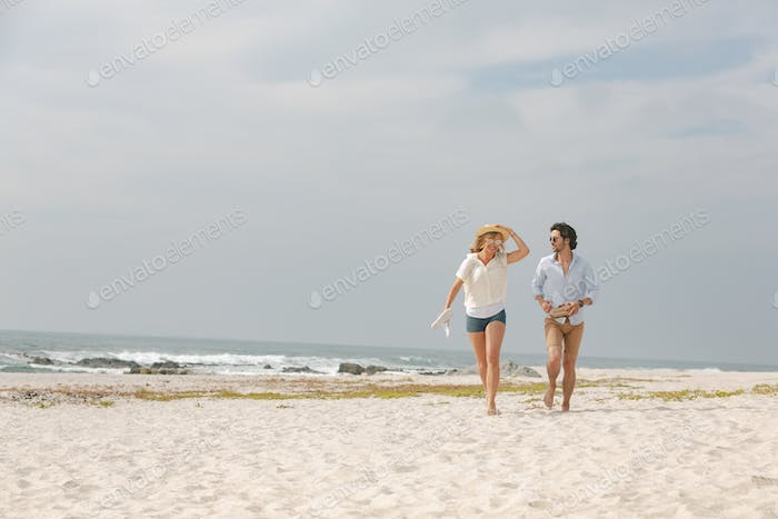 Front view of happy young Caucasian couple running at beach on a sunny day