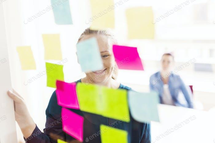 Smiling woman looking at adhesive notes