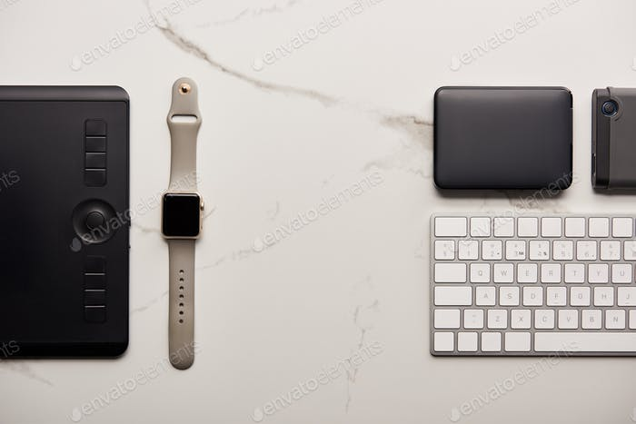 flat lay with graphics tablet with portable hdd, smart watch and wireless keyboard on white marble