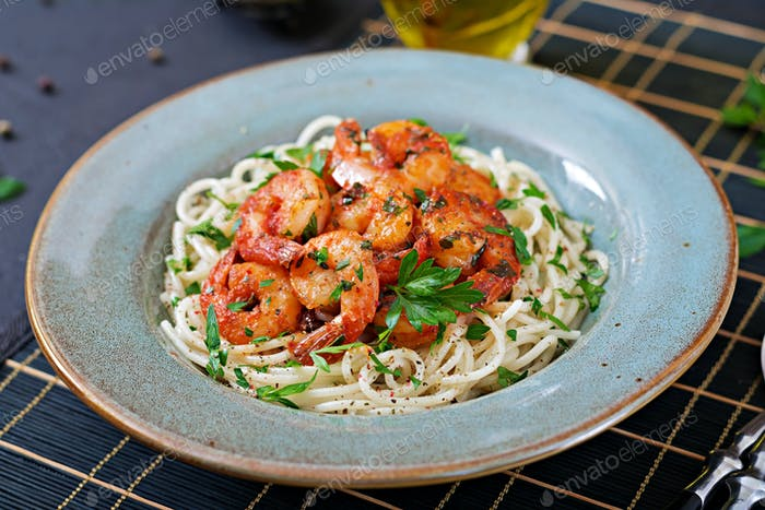 Pasta spaghetti with shrimps, tomato and chopped parsley. Healthy food. Italian meal.